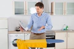 Uomo con ferro da stiro e la maglietta nella stanza della cucina Fotografia Stock