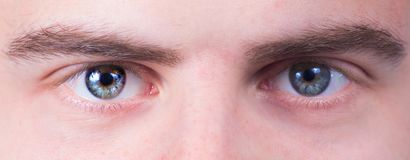 Uomo con gli occhi azzurri che esaminano la macchina fotografica, macro colpo fotografie stock libere da diritti