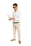Uomo con gli occhiali da sole che legge carta Fotografie Stock Libere da Diritti
