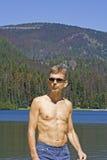 Uomo con gli occhiali da sole davanti ad un lago ed alle montagne Fotografia Stock Libera da Diritti