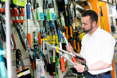 Uomo con gli strumenti di giardinaggio nel negozio fotografie stock