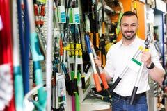 Uomo con gli strumenti di giardinaggio nel negozio Immagine Stock Libera da Diritti