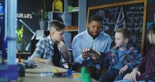 Uomo con i bambini che esplorano la mano meccanica di cartboard Immagini Stock
