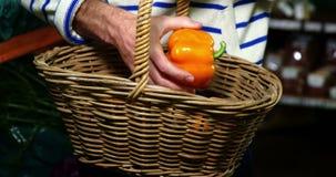 Uomo con i canestri che selezionano peperone dolce nella sezione organica stock footage