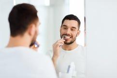 Uomo con i denti di pulizia dello spazzolino da denti al bagno immagini stock libere da diritti