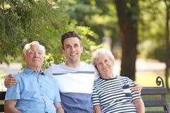 Uomo con i genitori anziani sul banco fotografia stock libera da diritti