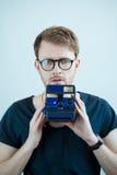 Uomo con i glases e la macchina fotografica della foto a disposizione Fotografie Stock Libere da Diritti