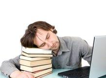 Uomo con i libri ed il sonno del computer portatile Fotografia Stock