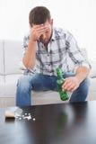 Uomo con i postumi della sbornia con una birra e la sua medicina presentata sul tavolino da salotto Immagini Stock