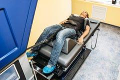 Uomo con i problemi dell'ernia spinale lombo-sacrale sull'allungamento e della fase di decompressione nel centro medico, terapia  Immagini Stock