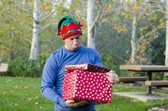 Uomo con i regali tristi della tenuta del fronte all'aperto che portano un maglione blu Immagine Stock Libera da Diritti