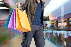 Uomo con i sacchetti di acquisto Fotografia Stock