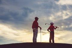 Uomo con i suoi giocatori di golf del figlio Fotografia Stock