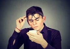 Uomo con i vetri che hanno difficoltà che vede i problemi di visione del telefono cellulare Fotografie Stock Libere da Diritti