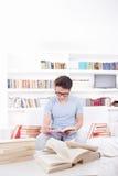 Uomo con i vetri che legge un libro sullo strato Immagine Stock