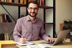 Uomo con i vetri che riscrittura dal suo computer portatile fotografia stock libera da diritti