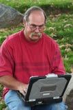Uomo con i vetri sul computer portatile Fotografie Stock Libere da Diritti