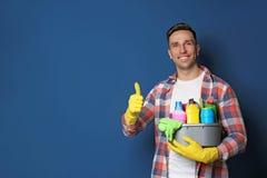 Uomo con il bacino dei detersivi sul fondo di colore immagini stock libere da diritti