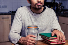 Uomo con il barattolo dell'inceppamento e la pila di libri Fotografia Stock
