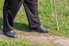 Uomo con il bastone da passeggio che cammina su una strada sterrata Fotografia Stock