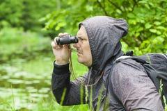 Uomo con il binocolo che guarda gli uccelli Fotografia Stock