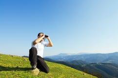 Uomo con il binocolo nella montagna. Fotografia Stock