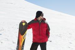 Uomo con il bordo dello sci che distoglie lo sguardo sulla neve Fotografie Stock