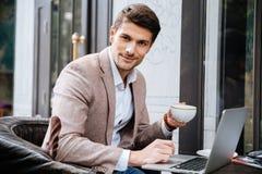 Uomo con il caffè di seduta e bevente del computer portatile in caffè all'aperto immagine stock
