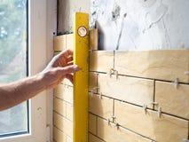 Uomo con il calibro che misura le linearità verticali di installazione cer Fotografie Stock Libere da Diritti