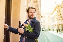 Uomo con il campanello di squillo del mazzo del fiore e del vino fotografie stock libere da diritti
