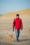 Uomo con il cane alla spiaggia Fotografie Stock