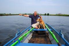 Uomo con il cane in barca Immagini Stock