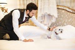 Uomo con il cane bianco sveglio Vestito da sposa che appende sul letto nella stanza Fotografia Stock