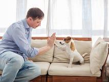 Uomo con il cane a casa Fotografia Stock
