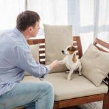 Uomo con il cane a casa Immagine Stock