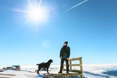 Uomo con il cane che riposa su un plateau nevoso delle montagne immagini stock libere da diritti