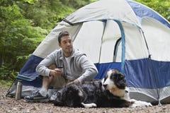 Uomo con il cane che si siede dalla tenda Fotografia Stock