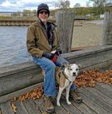 Uomo con il cane, sedentesi su un bacino Fotografia Stock