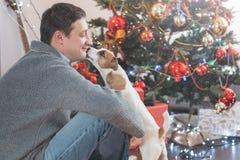 Uomo con il cane vicino all'albero di Natale fotografia stock