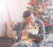 Uomo con il cane vicino all'albero di Natale fotografie stock libere da diritti