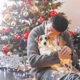 Uomo con il cane vicino all'albero di Natale fotografia stock libera da diritti