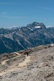 Uomo con il cappello che cammina in percorso di pietra fra le montagne sterili nelle alpi italiane delle dolomia nell'ora legale Immagini Stock Libere da Diritti