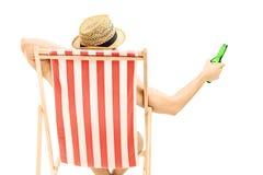 Uomo con il cappello che si siede su una sedia di spiaggia e che tiene una bottiglia di birra Immagine Stock Libera da Diritti