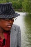 Uomo con il cappello davanti al fiume immagini stock libere da diritti