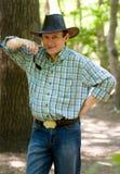 Uomo con il cappello di cowboy nella foresta Immagini Stock