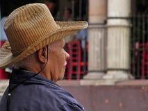 Uomo con il cappello rilassato e che guarda fisso nel centro della città di San Miguel de Allende Fotografia Stock