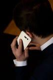 Uomo con il cellulare che si siede ad un funzionamento della tavola Fotografia Stock Libera da Diritti