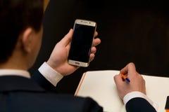 Uomo con il cellulare che si siede ad una tavola che lavora al suo taccuino Fotografie Stock Libere da Diritti