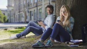 Uomo con il cellulare che si siede sotto l'albero e che esamina ragazza che per mezzo del telefono, affetto fotografia stock libera da diritti