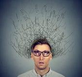 Uomo con il cervello preoccupato di espressione del fronte che si fonde nelle linee punti interrogativi fotografie stock